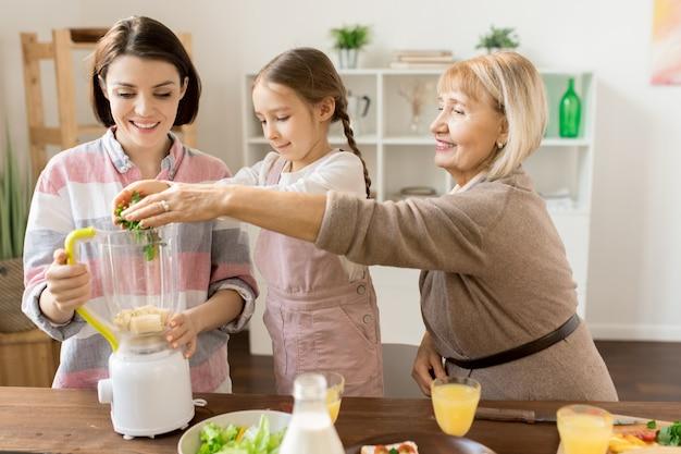 Reife frau und ihre enkelin geben frisches grünes gemüse in den mixer und bereiten smoothie für die ganze familie zu