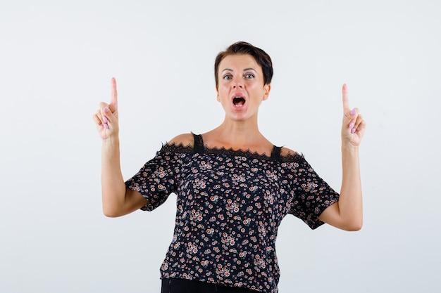 Reife frau zeigt mit zeigefingern nach oben, hält den mund in blumenbluse, schwarzem rock offen und sieht überrascht aus. vorderansicht.
