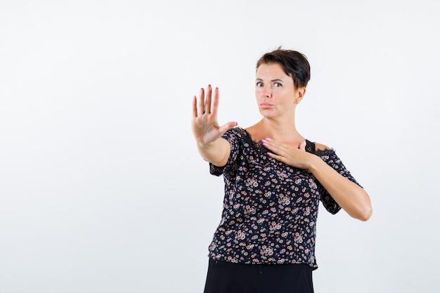 Reife frau zeigt stoppschild, hält hand über brust in blumenbluse und schwarzem rock und sieht ernst, vorderansicht.