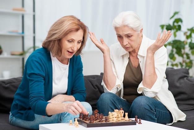 Reife frauen, die zusammen schach spielen