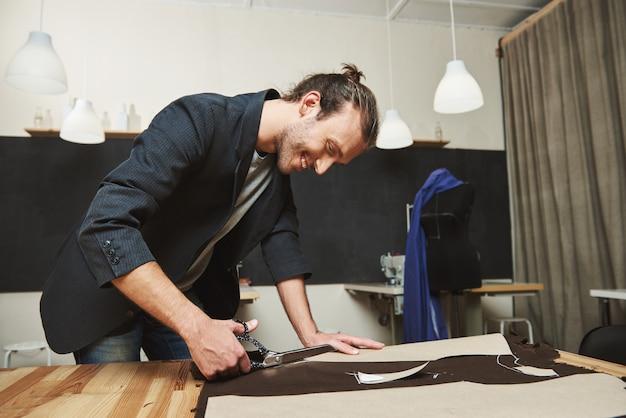 Reife freudige attraktive dunkelhaarige hispanische, männliche modedesignerin, die in der werkstatt an einem neuen kleid arbeitet, teile ausschneidet, muster macht, teile zusammennäht.