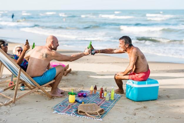 Reife freunde, die bier am strand trinken