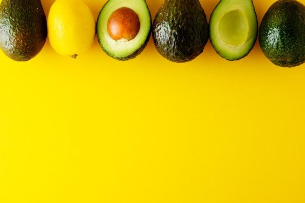 Reife frische avocado lokalisiert auf gelbem hintergrund. avocado isoliert. kopieren sie platz.