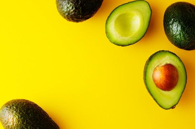 Reife frische avocado lokalisiert auf gelbem hintergrund. bunter gesunder nahrungsmittelhintergrund. avocado isoliert.