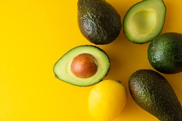 Reife frische avocado lokalisiert auf gelbem hintergrund. bunter gesunder nahrungsmittelhintergrund. kopieren sie platz.