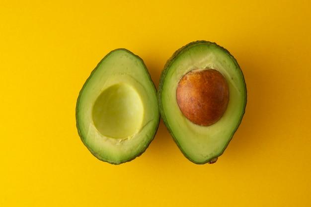 Reife frische avocado slaces lokalisiert auf gelbem hintergrund. bunter gesunder nahrungsmittelhintergrund.