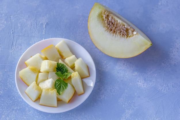 Reife frische gelbe melone in stücke geschnitten auf blau