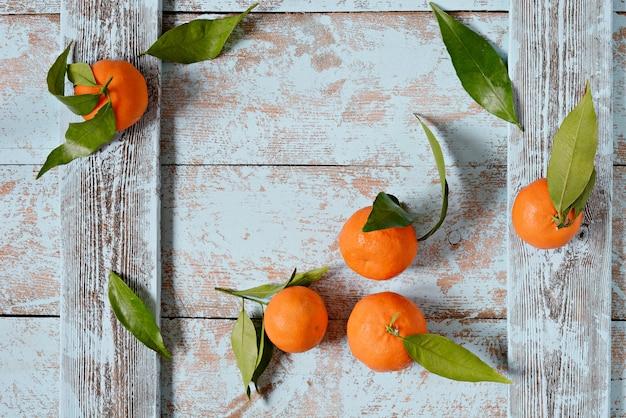Reife frische mandarinen mit blättern auf einem hölzernen blauen hintergrund. obsthintergrund, veganes essen.