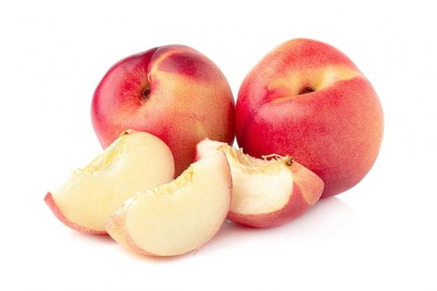Reife frische nektarinenfrucht und halbe nektarinenfrucht lokalisiert auf weißem hintergrund.