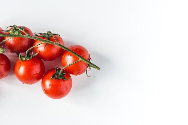 Reife frische rote kirschtomaten auf einem weißen hintergrund
