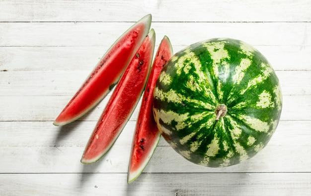 Reife frische wassermelone auf weißem holztisch.