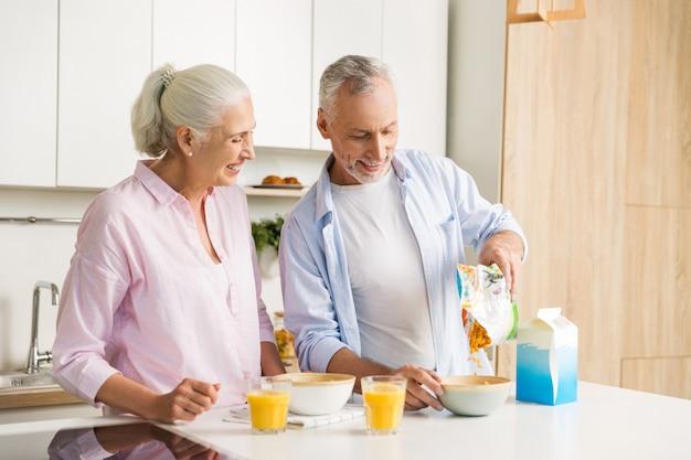 Reife fröhliche liebespaarfamilie, die saft trinkt, der cornflakes isst