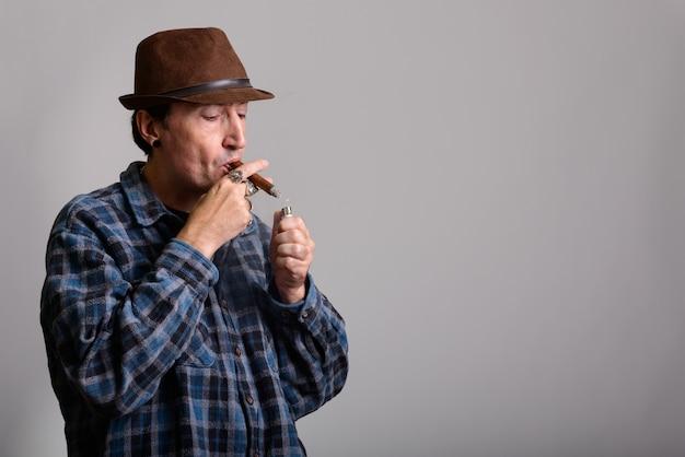 Reife gangster mann beleuchtung beim rauchen zigarre