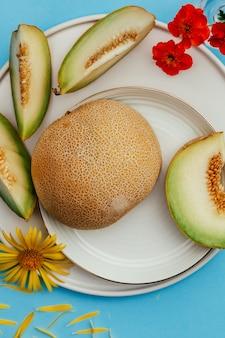 Reife ganze melone und auf einem blauen tisch in scheiben geschnitten