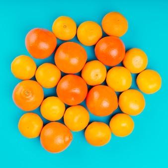Reife ganze orangen auf türkisfarbenem hintergrund