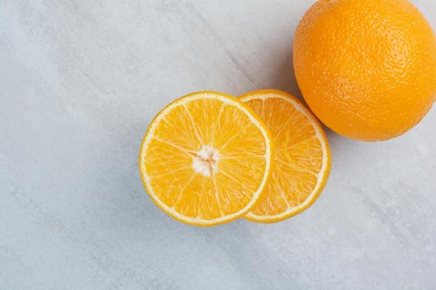 Reife ganze und halb geschnittene orangen auf steinhintergrund. foto in hoher qualität
