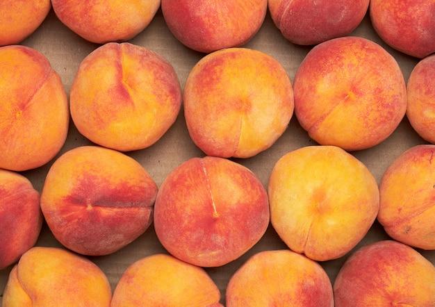 Reife gelb-rote runde pfirsiche liegen in einer reihe