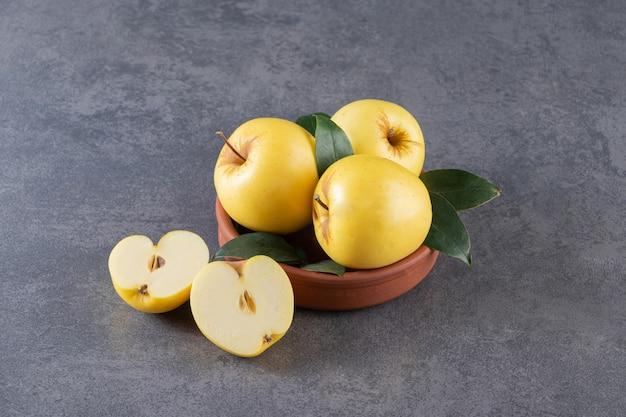 Reife gelbe äpfel mit grünen blättern in tonschale.