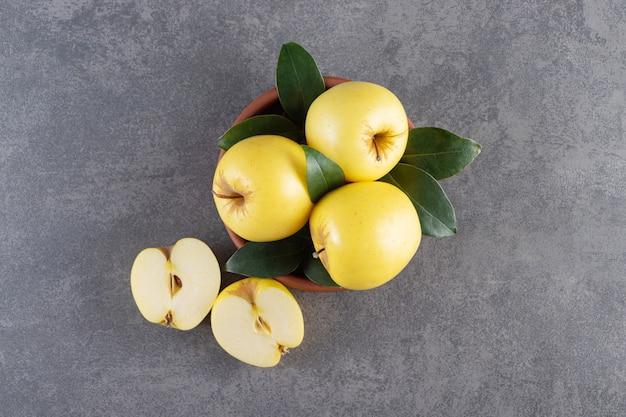 Reife gelbe äpfel mit grünen blättern in tonschüssel.