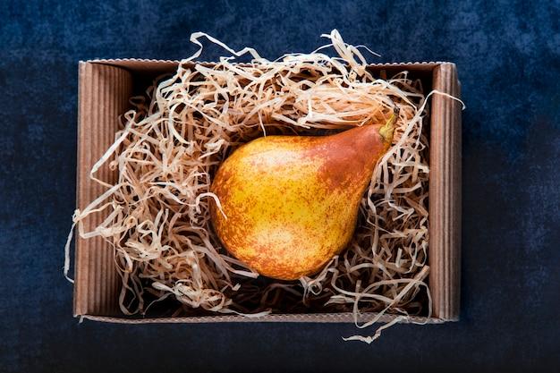 Reife gelbe bera-birne in umweltfreundlicher kartonverpackung und heu