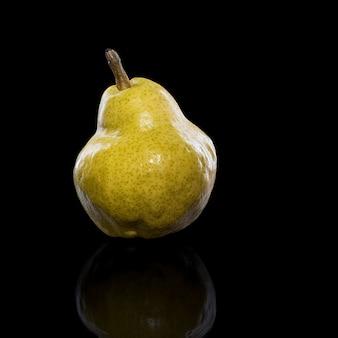 Reife gelbe birnenfrucht, mit reflexion in schwarzer oberfläche, isoliert auf schwarz