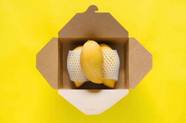 Reife gelbe thailand-barrakuda-mangos mit schaumgitter, das in papierbox auf gelbem hintergrund gelegt wird.