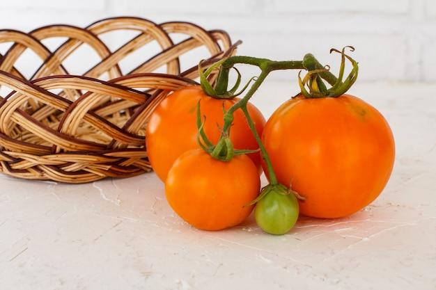 Reife gelbe tomaten der nahaufnahme und ein weidenkorb auf dem weißen strukturierten hintergrund. zutaten für vegetarisches essen.