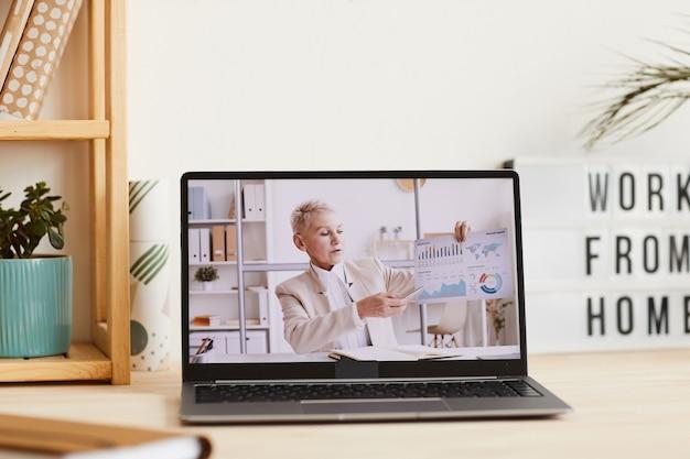 Reife geschäftsfrau, die auf diagramme in ihrer hand zeigt und über finanzielle situation während der online-geschäftskonferenz spricht