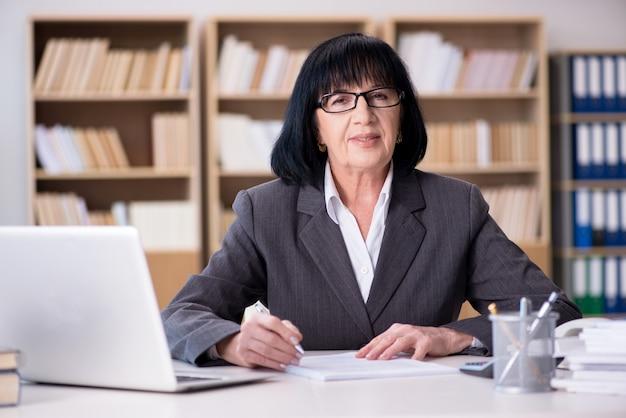 Reife geschäftsfrau, die im büro arbeitet