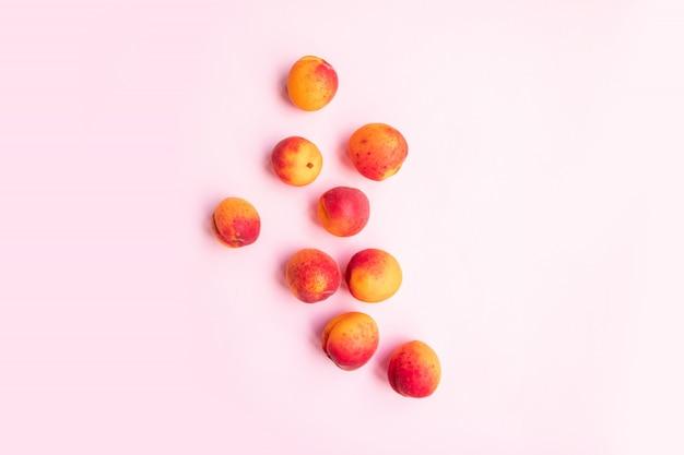 Reife geschmackvolle pfirsiche der flachen zusammensetzung mit roter seite auf einem rosa hintergrund.