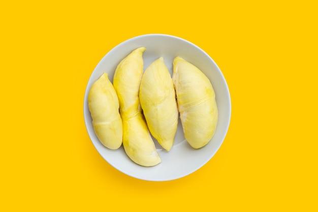 Reife geschnittene durian in weißer platte auf gelbem hintergrund.