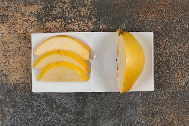 Reife geschnittene quitte auf weißem quadratischem teller