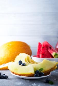 Reife geschnittene wassermelone und melone lokalisiert auf grau