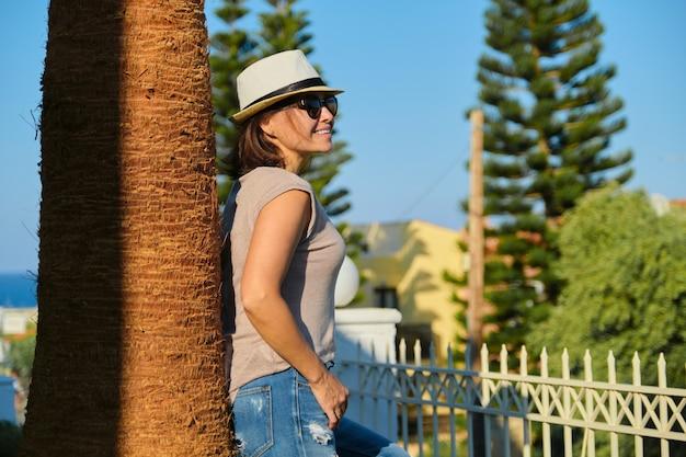 Reife glückliche schöne frau im sonnenbrillenhut, der nahe palme auf sonnenuntergang steht