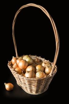 Reife goldene zwiebel in einem weidenkorb auf schwarzem hintergrund. eine zwiebel neben dem korb. vertikal