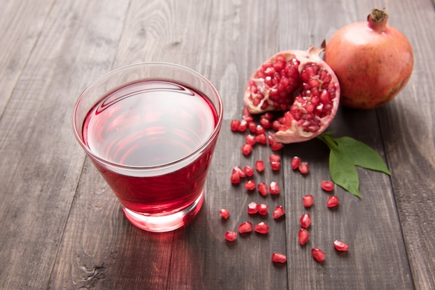 Reife granatäpfel mit saft auf holztisch