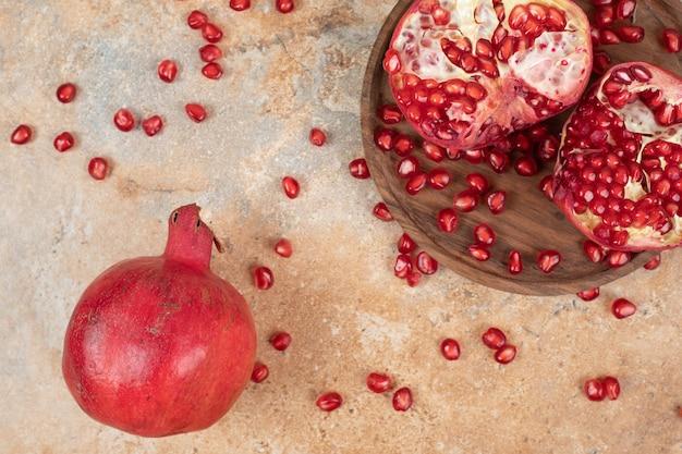 Reife granatäpfel und samen auf marmoroberfläche.