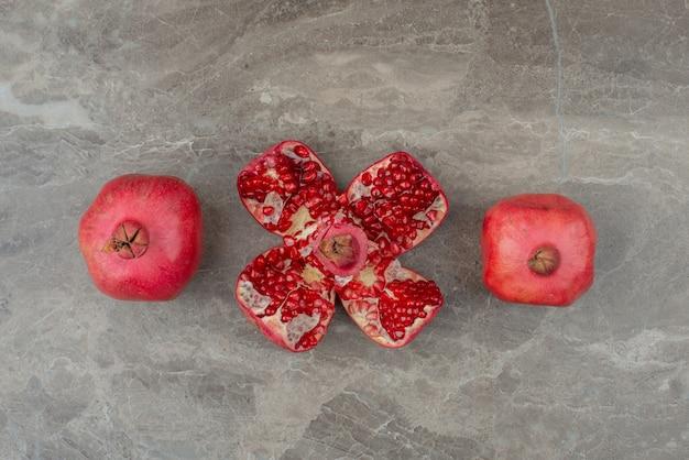 Reife granatäpfel und samen auf marmortisch.