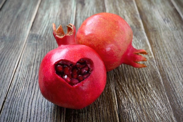 Reife granatapfelfrucht hautnah auf hölzernem hintergrund. konzept für gesunde ernährung. auf der granatapfelhaut in herzform ausschneiden.