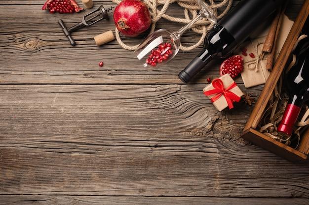 Reife granatapfelfrucht mit einem glas wein, einer flasche und einem geschenk auf einem hölzernen hintergrund