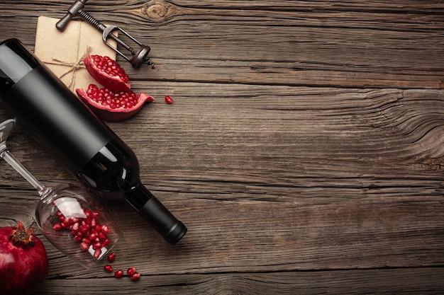 Reife granatapfelfrucht mit einem glas wein, einer flasche und einem korkenzieher auf einem hölzernen hintergrund