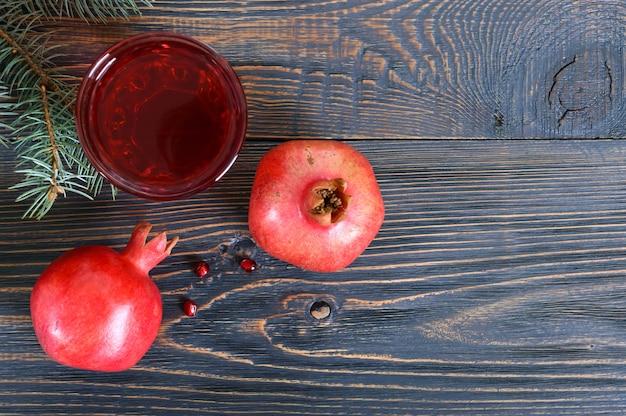 Reife granatapfelfrüchte und ein glas granatapfelsaft auf holztisch. konzept für gesunde ernährung. die draufsicht