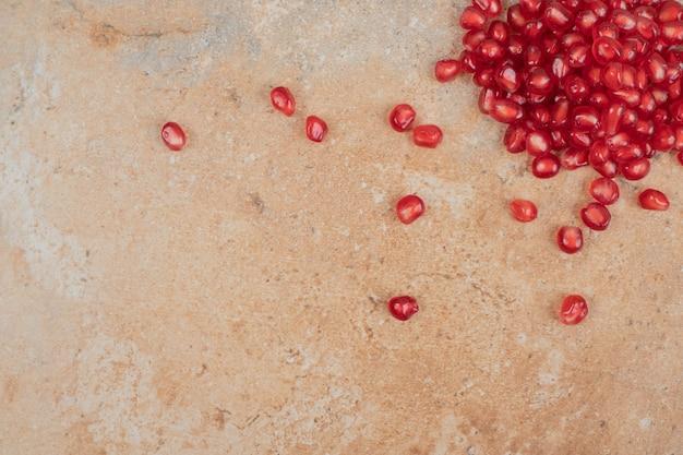 Reife granatapfelkerne auf marmorhintergrund.