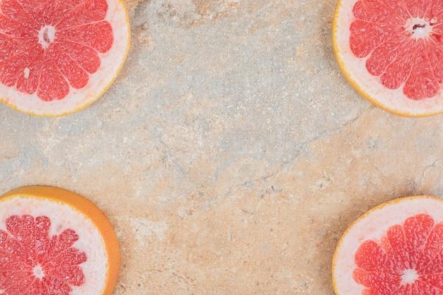 Reife grapefruitscheiben auf marmoroberfläche. hochwertiges foto