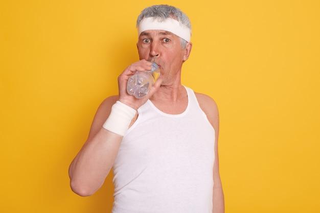 Reife grauhaarige männliche kleider weißes stirnband und ärmelloses t-shirt, trinkwasser während des körperlichen trainings,