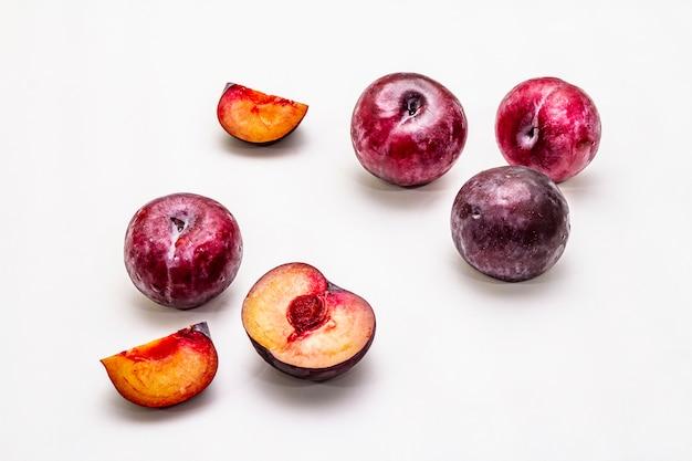 Reife große lila pflaumen. frische ganze früchte, halb geschnitten, samen.