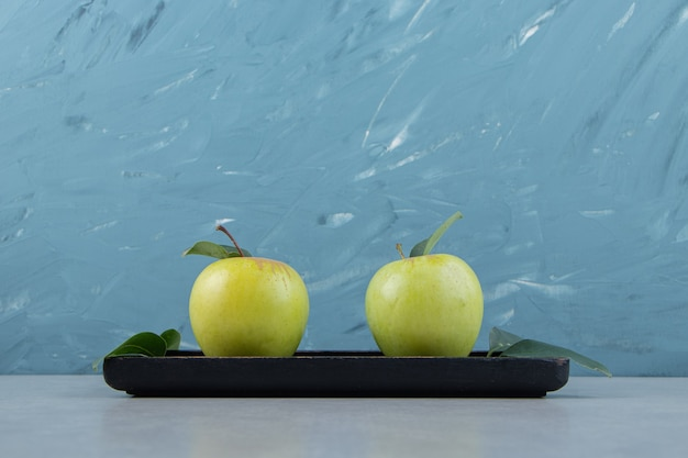 Reife grüne äpfel auf schwarzem teller.