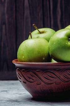 Reife grüne äpfel in einer schüssel auf einem dunklen hintergrund