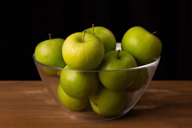 Reife grüne äpfel in einer transparenten schüssel