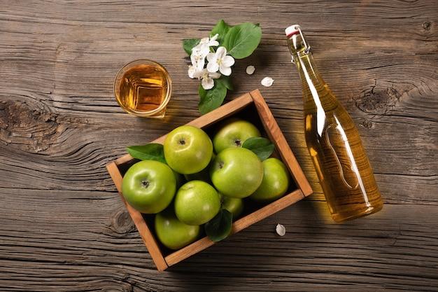 Reife grüne äpfel in holzkiste mit zweig aus weißen blumen, glas und flasche apfelwein auf einem holztisch. ansicht von oben.
